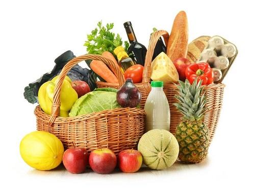Sur l'image on voit un panier rempli de fruits et de légumes. On y voit également du fromage et des bouteilles. Le végétarisme est un régime alimentaire pouvant intégrer tous ces aliments.