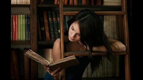 Sujet : Éducation financière. L'image montre une femme qui lit un livre dans une bibliothèque.